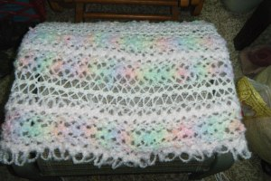 Baby blanket.  Need to finish the sides.  Done with the hairpin lace part.  3 types of yarn, all fuzzy.